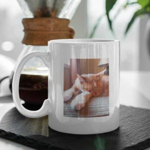 Ceramic mug on table with a picture of cat printed on to it