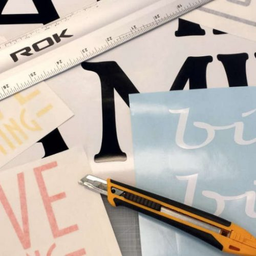 Vinyl lettering shown with knife and ruler on table